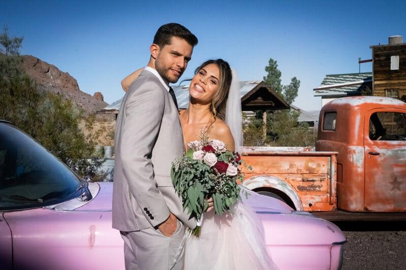 Un jeune couple marié se tient devant une vielle cadillac rose et un camion ancien dans un village fantôme abandonné