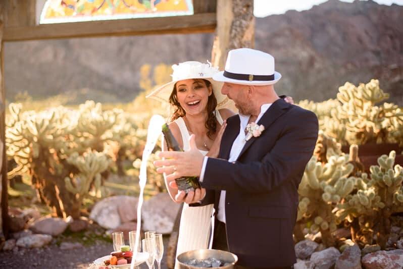 Deux mariés ouvrent une bouteille de champagne après s'être dit oui aux USA