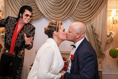 couple kissing in a wedding chapel in front of Elvis