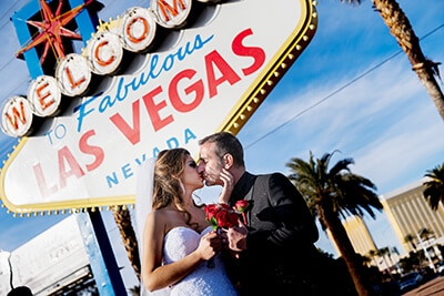 Couple kissing in front of the Vegas Sign