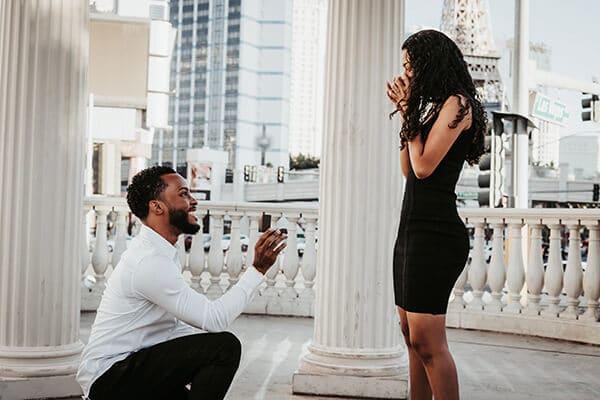Homme à genoux devant sa fiancée pour sa demande en mariage pendant un shooting photo à Vegas